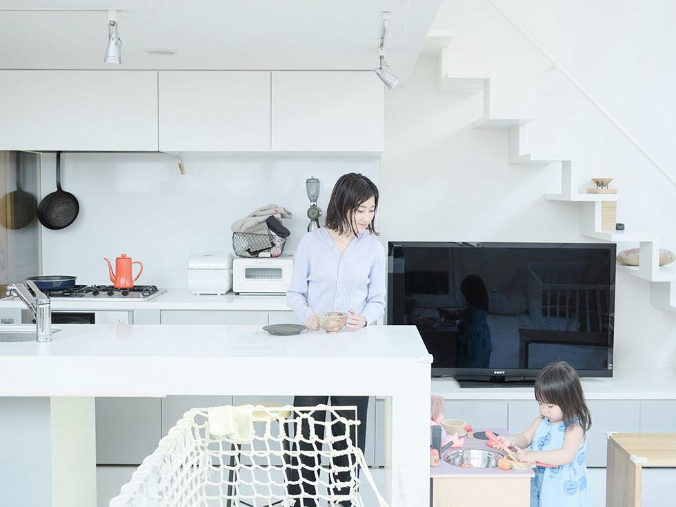 キッチンで料理をするママのそばでままごとをする女の子